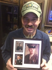 Jon (Desert Storm combat vet) holding Service photos of himself, his brother, and their dad