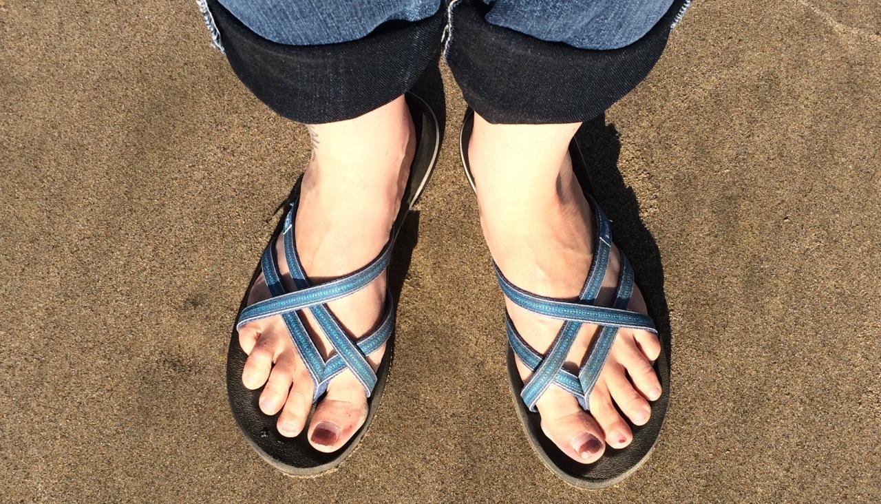 sandaled feet on the sandy beach
